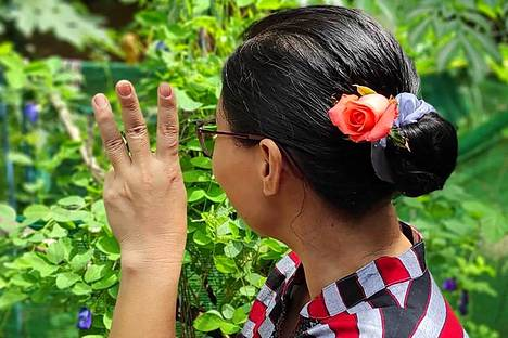 The supporter placed a flower in his hair to remember Aung San Suu Kyi, who was under house arrest.