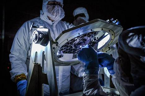 Space engineers inspect the technology to be installed in the James Webb space telescope.
