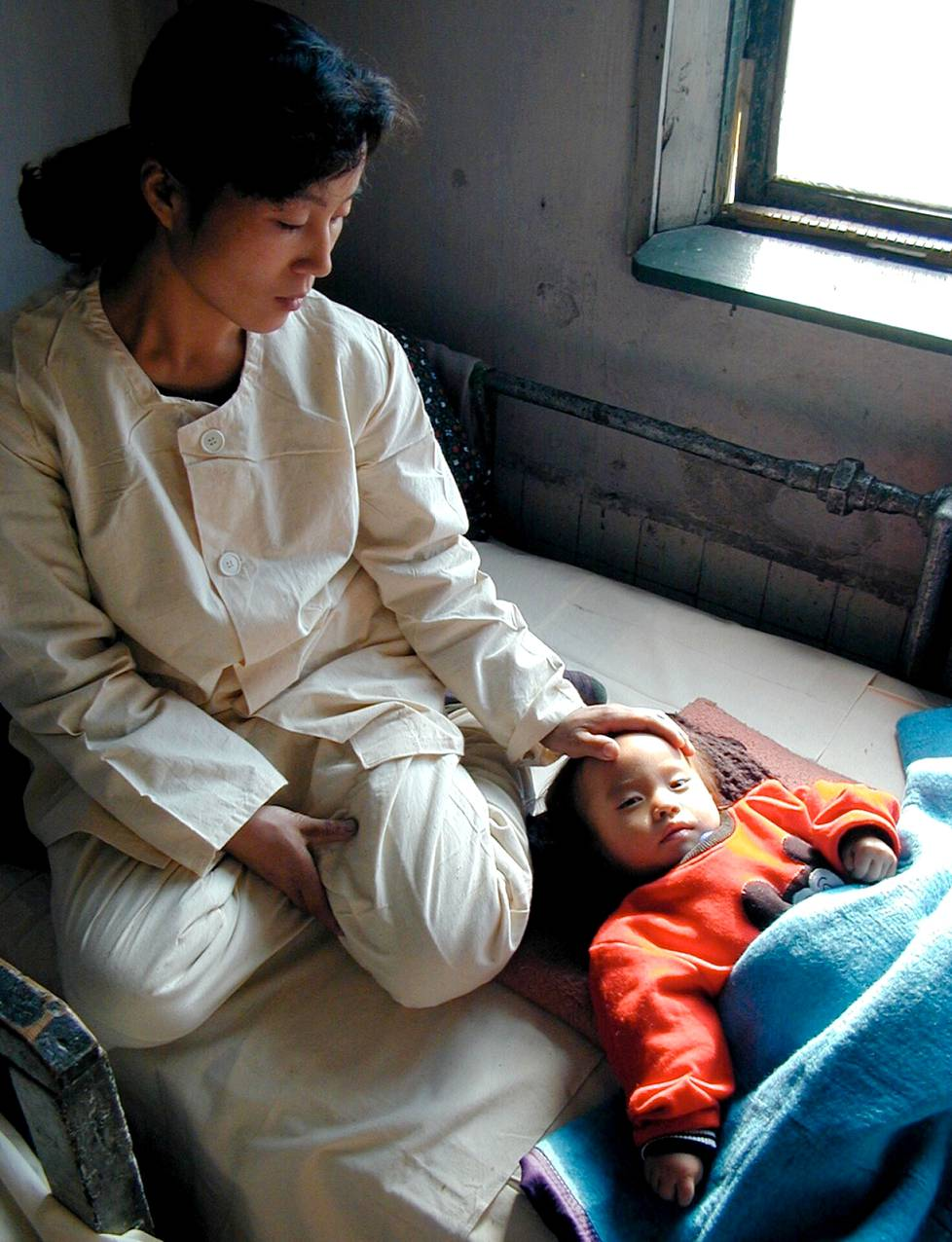 The mother stroked her malnourished child in December 1999, when North Korea was suffering from a severe famine.  The current difficult situation is believed to affect children and other vulnerable sections of the population in particular.