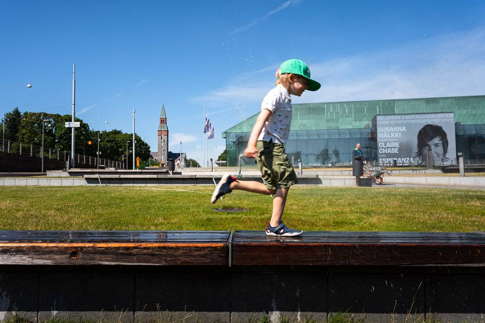 Four-year-old Kaapo K. ran under the sprinkler in front of the Music Hall.  Kaapo was on his way to the movies with his mother, and on the way were changing clothes to replace the wet ones.