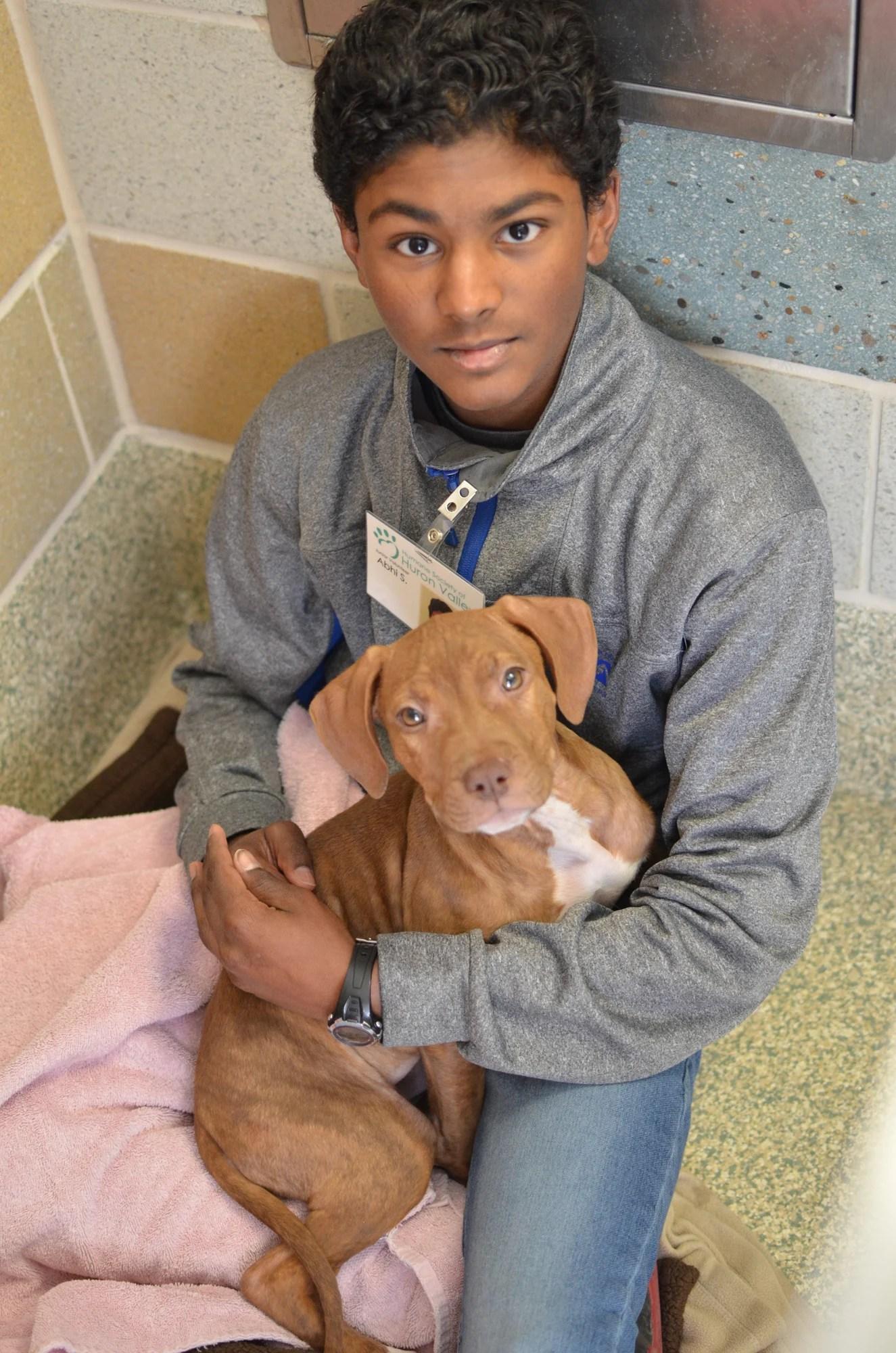 Junior volunteer with a puppy
