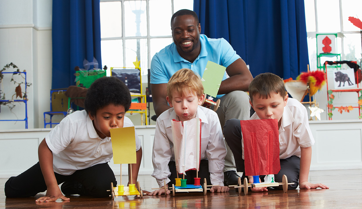 stock image of boy students in science class with teacher