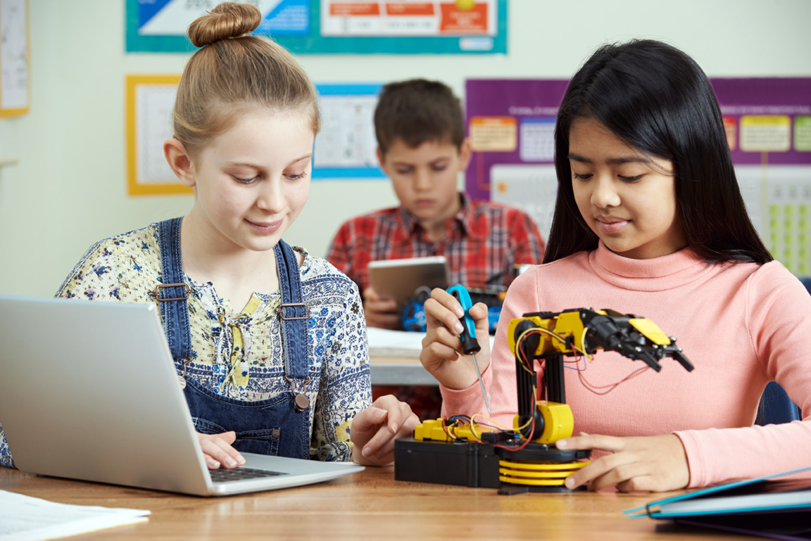 stock image of pupils studying robots in science class