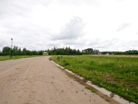 Empty streets surrounded by bulldozed landscape.