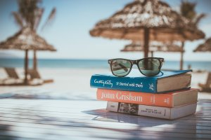 Picture of books with sunglasses, tiki huts on beach in background