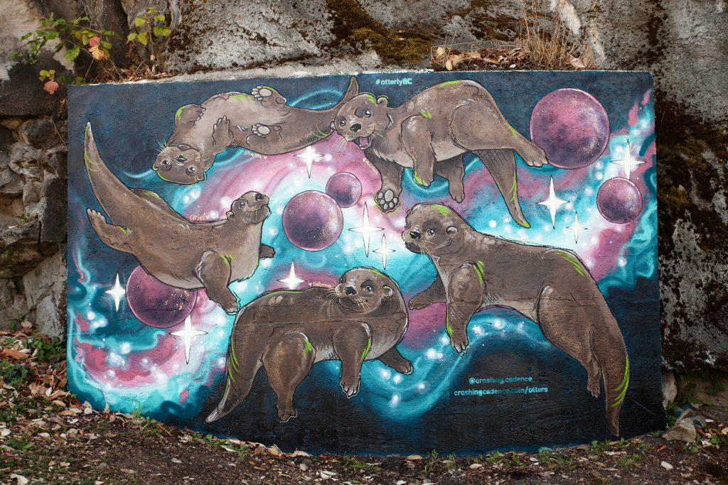 Mural of spry otters frolicking through a galaxy background, titled ' Adventures In Otter Space'