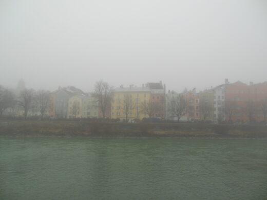 Blick auf die bunten Häuser auf der anderen Seite des Inn im Nebel