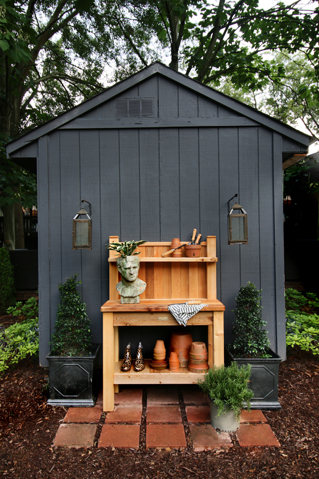 black garden shed with cedar potting bench