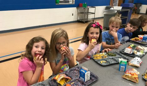 A group of elementary students at lunch biting into apples.