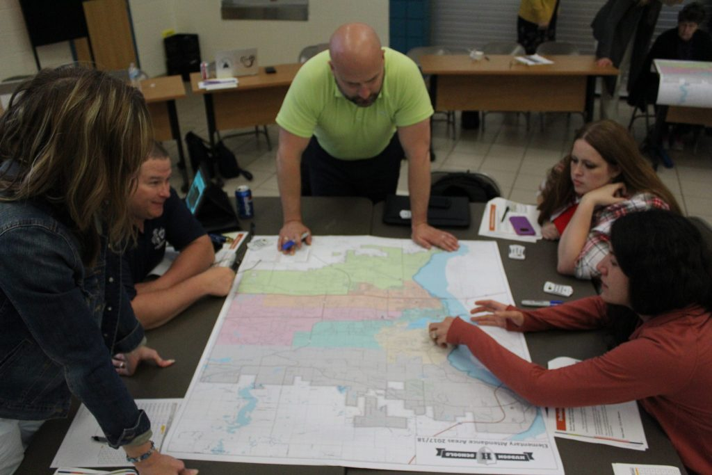 A group of committee members discuss the boundaries on a large map on their table.