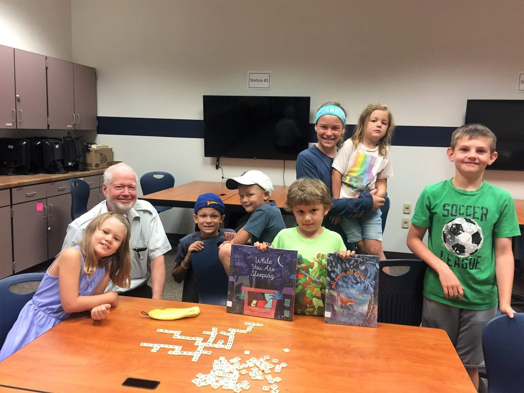 A group of elementary students sit around a table with a community volunteer playing word games.