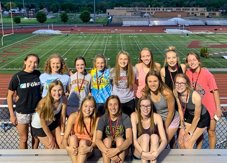 Girls track and field members gathered on the bleachers.