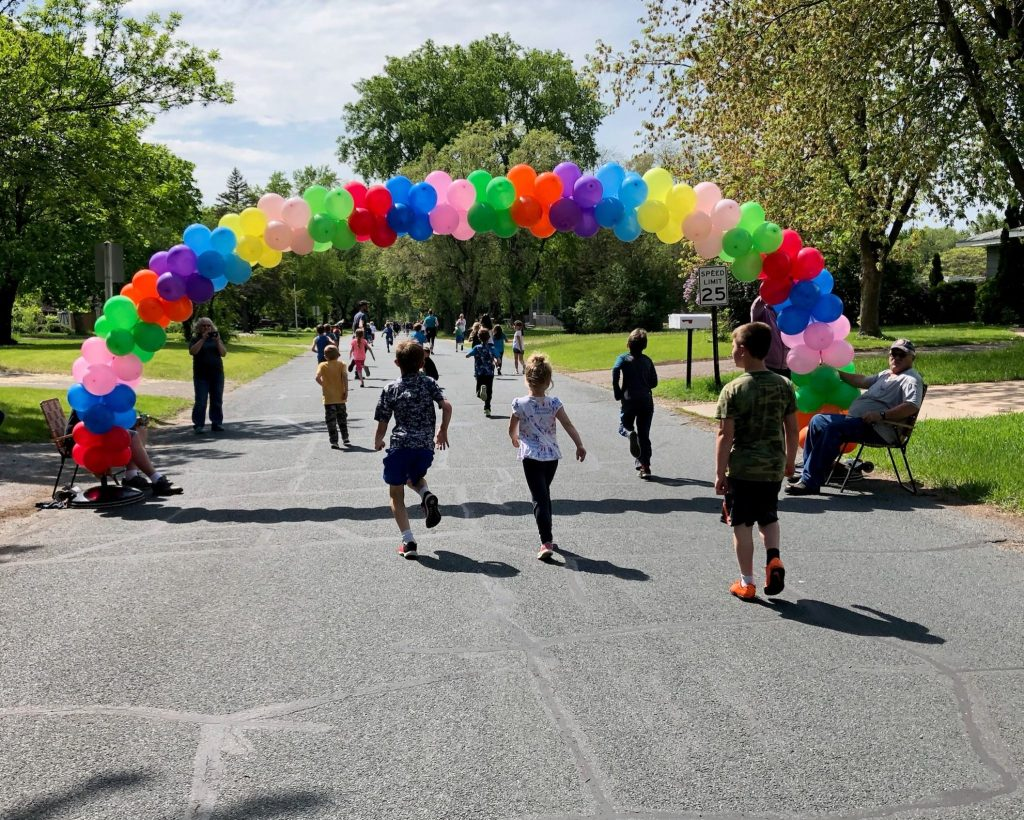 A group of students running down the street through a rainbow balloon arch.