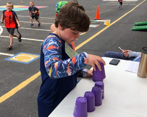 A student stacking purple plastic cups.