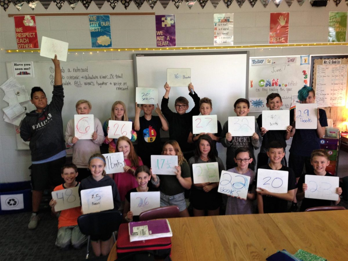 A large group of students hold up sheets of paper with the number of books they read.