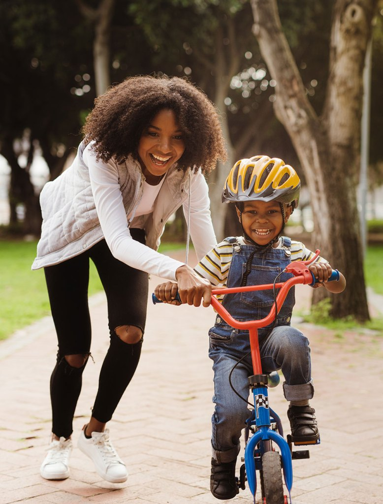 Mom teaching son to ride a bike - Plan for their future with Child Plan