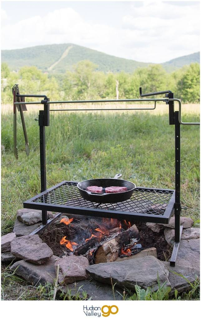 Cooking steaks in a cast iron skillet over a campfire at a Tentrr campsite