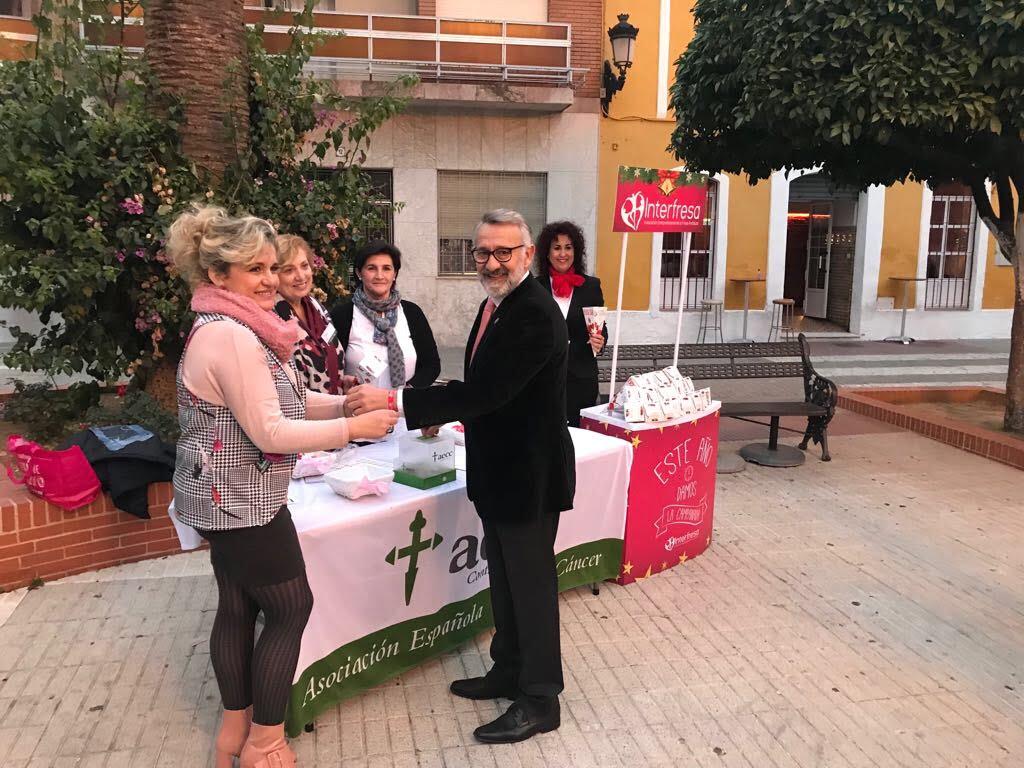 El alcalde de Bonares, tras recoger los cartuchos de fresas y hacer entrega del donativo para la AECC, recibió la pulsera solidaria aportada por Fundación Caja Rural del Sur.