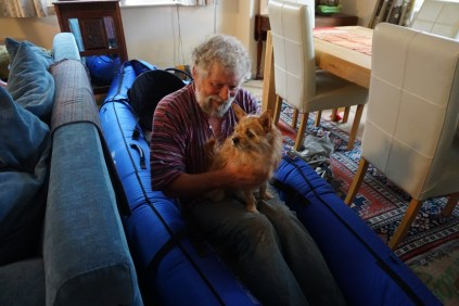 Dog and man in inflatable kayak in a dining room