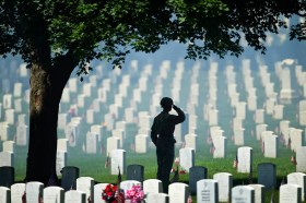 """With artillery smoke hanging in the air from a 21-gun salute by his company at Fort Leavenworth, the 500th Military Police Detachment, Army Sgt. Travis Smith saluted during the playing of """"Taps,"""" during Monday's Memorial Day ceremony at Fort Leavenworth National Cemetery. DAVID EULITT/The Kansas City Star"""