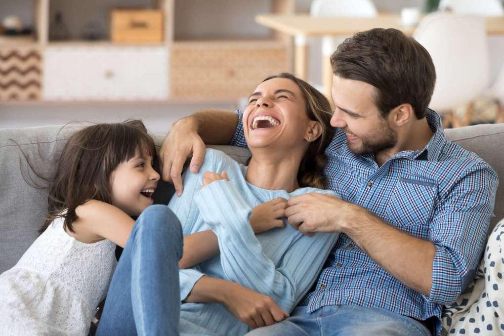 Kind und Eltern lachen entspannt