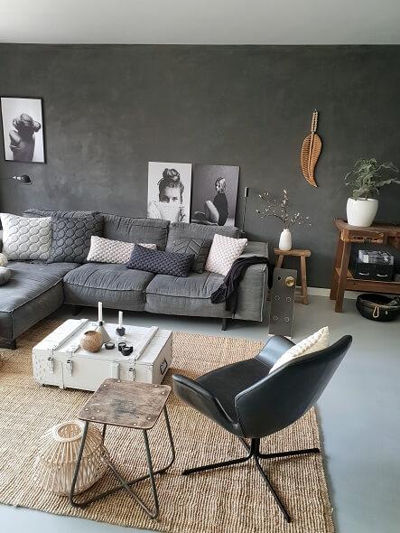 woonkamer grijze bank zwarte muur betonlook