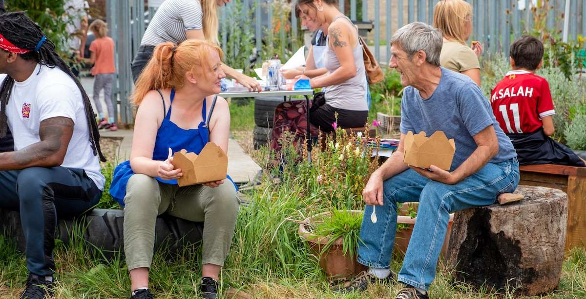 Photo shows two people sitting on haybales during the outdoor feastival event. They are eating from cardboard takeaway boxes and facing each other smiling.