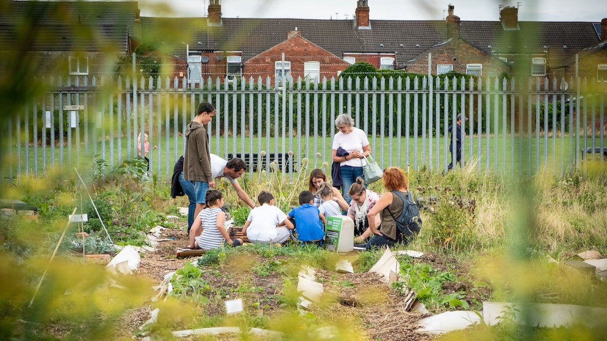 Photo shows a group of children sitting on the ground together learning.