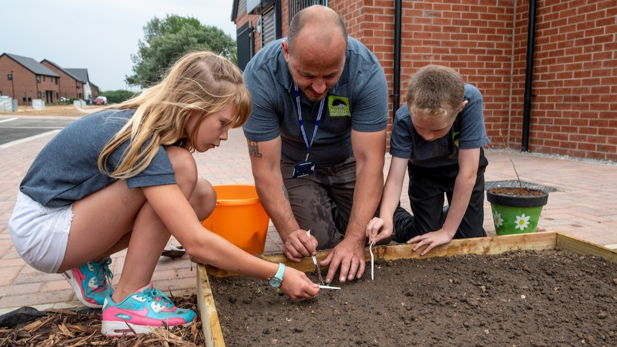 Photo of two children and an adult examining the soil in a raised bed