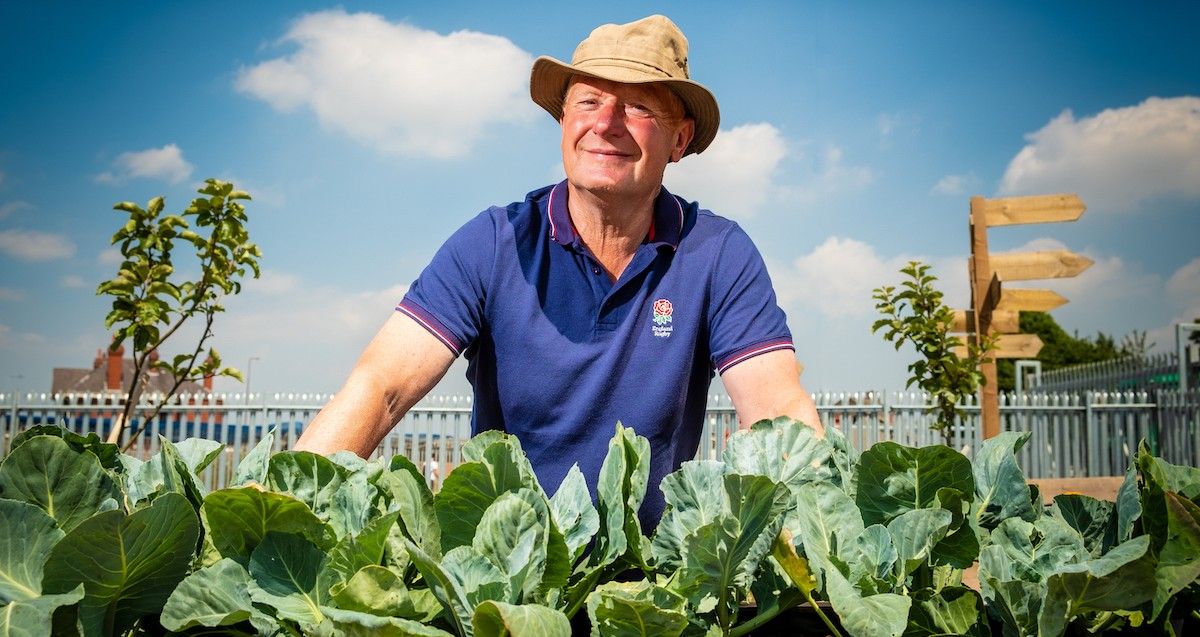 A man wearing a hat is sitting in front of a bright blue sky. In front of him, obscuring his legs, there is a row of green cabbages growing.