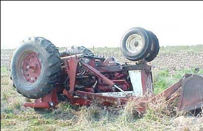Photo 1 – Tractor without ROPS at scene of overturn. Note the rocks spilled from the loader bucket and height of the loader bucket relative to the tractor's hood.