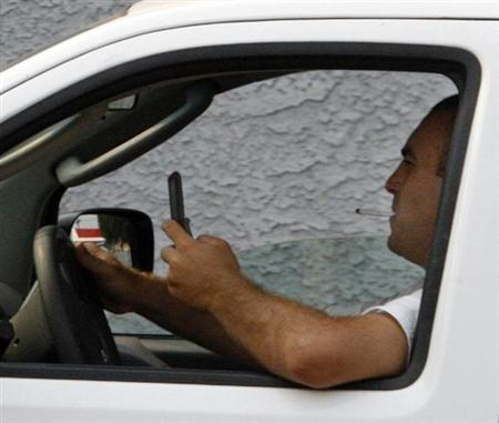 A man uses a cell phone while driving in Burbank, California June 25, 2008. Credit: Reuters/Fred Prouser