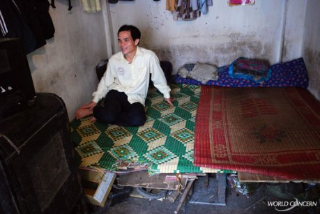 Migrant workers like this man pay about $10 a month to share a small room with 3 other people.