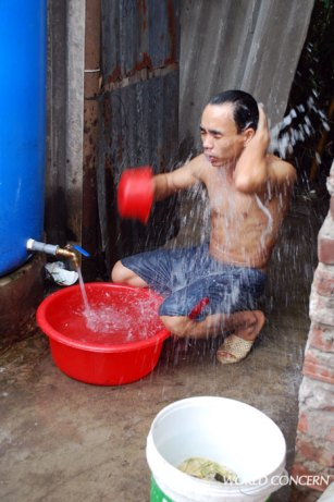 Clean water is a new blessing in this Hanoi slum. People bathe, wash clothes, and prepare food, all within a few square feet.