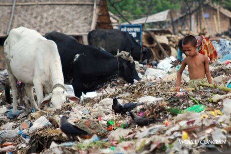 A boy wades through a festering trash pile in Bangladesh, looking for food. Humanitarian organization World Concern is working nearby, improving opportunities in the neighborhood with small business funding.