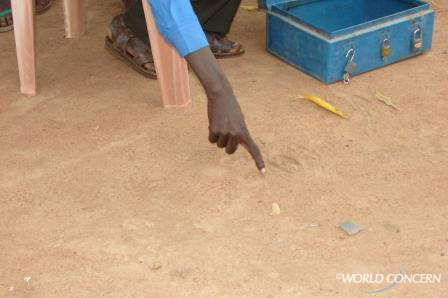 Sudanese villagers do quick calculations in the dirt.