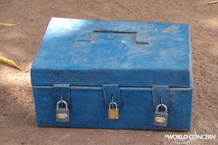 Three people are needed to open the three padlocks on this savings box, ensuring accountability.