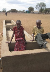 Kids play in a dry water trough.
