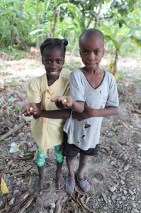 Belony and her brother in Haiti relieve deworming medicine.