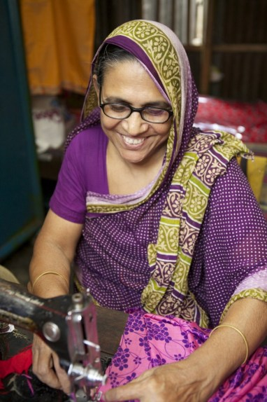 This woman in Bangladesh earns income by using her skills as a seamstress.