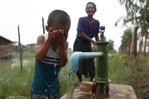 A child drinks clean water from a pump