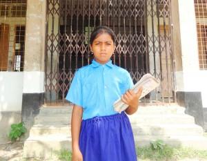 Mitu, now 8 years old, in front of her school.