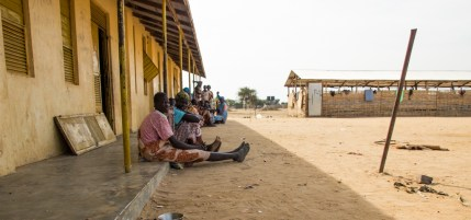 Women sit outside of the school where Mary gave birth.
