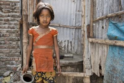 A girl stands by one of the slum's few latrines.