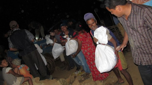 Emergency supplies being unloaded into Lok's village in the middle of the night.