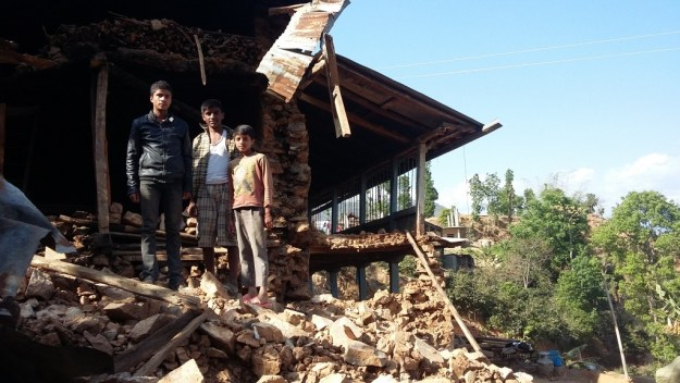 A family stands in front of their crumbled home in Bhotechaur village.