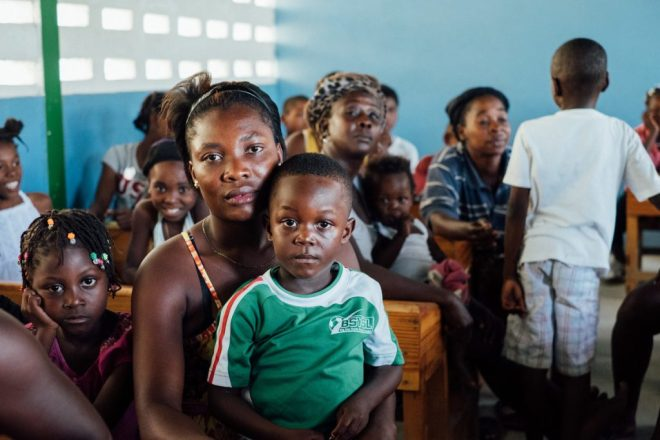 a mother and her son wait to receive deworming medicine in Haiti