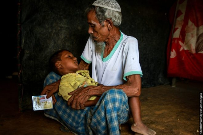 A Rohingya refugee sits with a little boy in a camp in Bangladesh