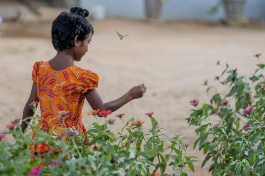 A young girl plays in a garden outside a children's home in Sri Lanka