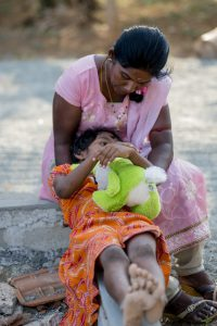 A social worker comforts a little girl in a children's shelter.